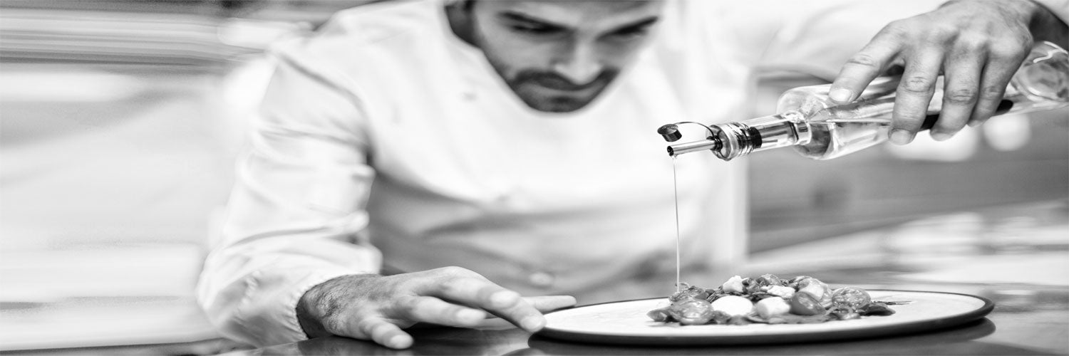 Chef pouring olive oil on salad.