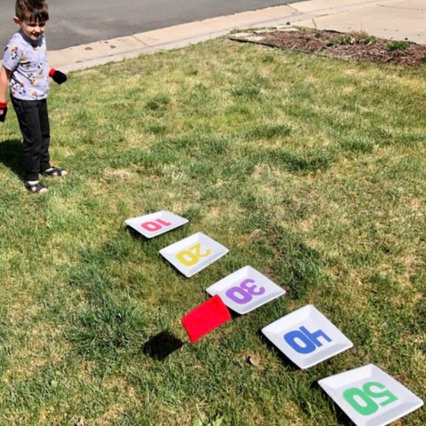 Kids Playing Bean Bag Toss Field Day At Home