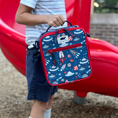 Child Holding Out To Lunch Blast Off lunchbox in color blue with rocket ship pattern while standing on playground