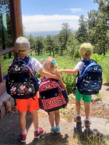 Kids hiking with Dino Dig, Heart Burst, and Aviator Camo backpacks