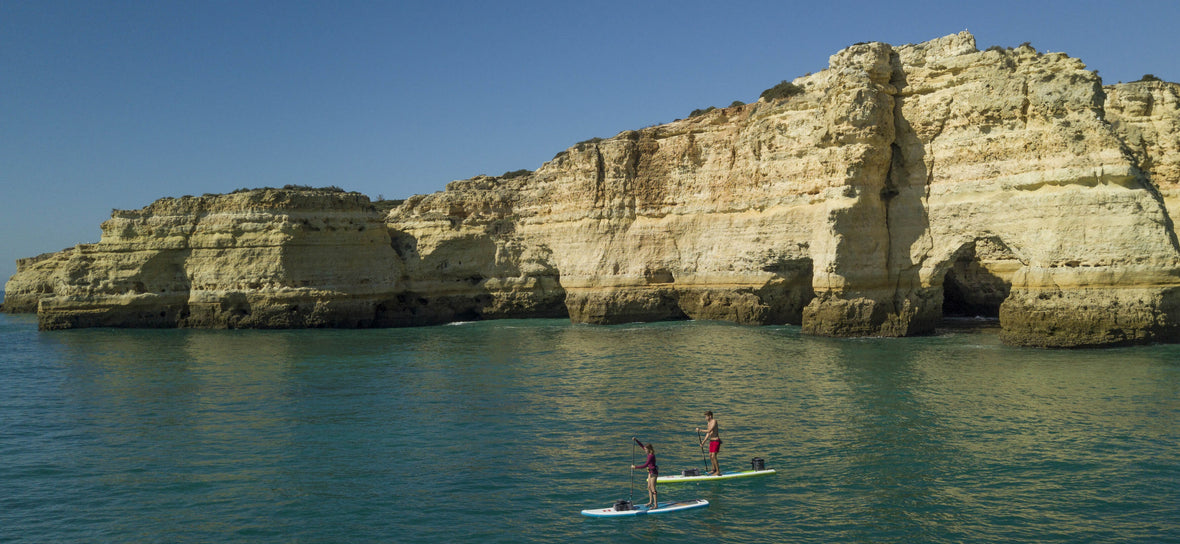 2 people paddle boarding in front of a cliff