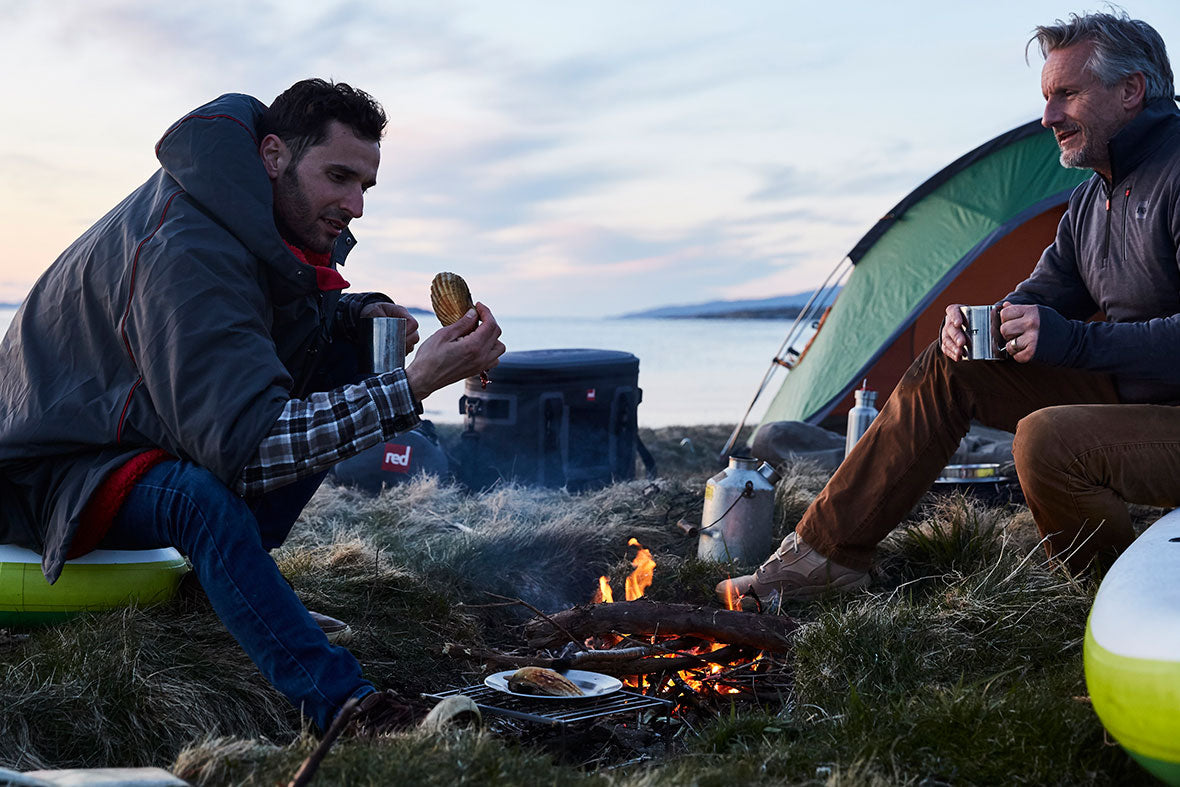 2 Men Enjoying Food By A Campfire On A Beach.
