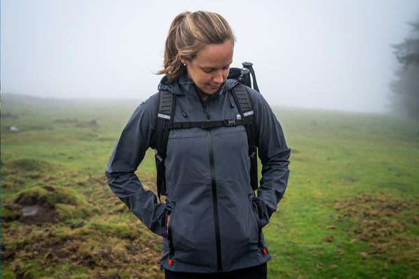 Woman wearing a waterproof active jacket and carrying a 30L Backpack standing in a field