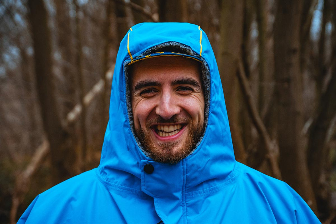 Man wearing Red Original Waterproof Changing Robe In Blue while in a wooded area
