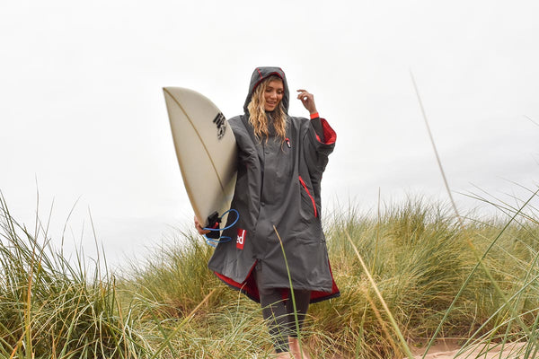 Woman in a Red Original Changing Robe Carrying A Surfboard