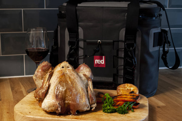 The Red Original Cooler Bag Bhind A Cooked Christmas Turkey With Vegetables And A Glass Of Wine