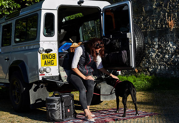Women with Dog sat outside a landrover
