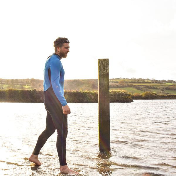 Man wearing wetsuit walking into water