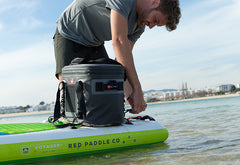 Man loading waterproof cool bag on to stand up paddle board