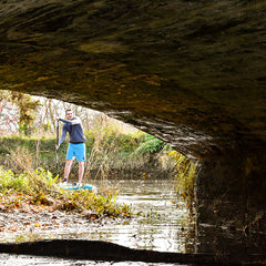 Man paddling under bridge