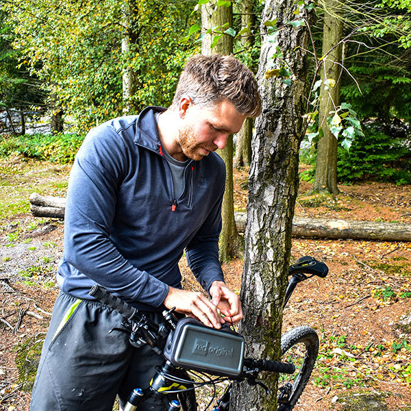 Male wearing Long Sleeve Performance top whilst fixing Dry Pouch to bike
