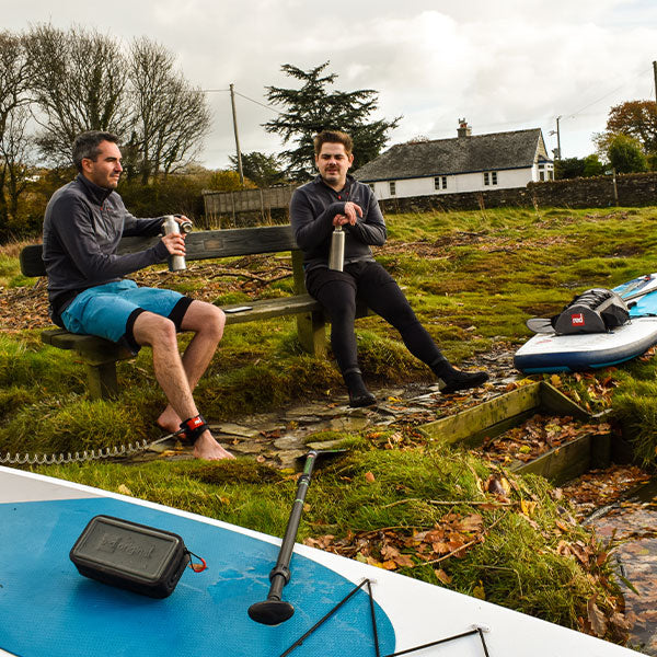 Two Males sat on bench with inflatable paddle board