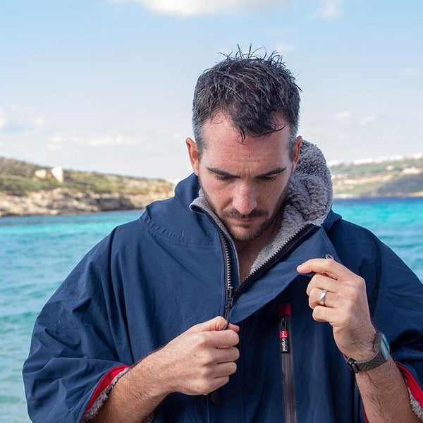 man unzipping Red Original Men's Pro Change Jacket at the beach