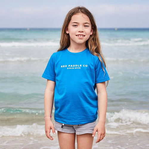Girl standing on a beach wearing the blue Red Paddle Co Since 2008 Kids T-shirt
