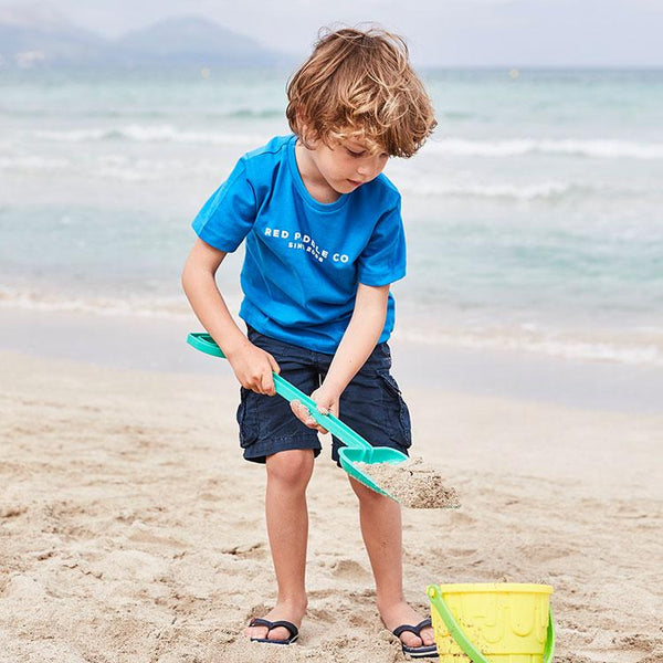 Young boy playing on the beach with a bucket and spade