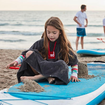 Child wearing Kid's Luxury Kids Poncho Towel Change Robe on paddleboard