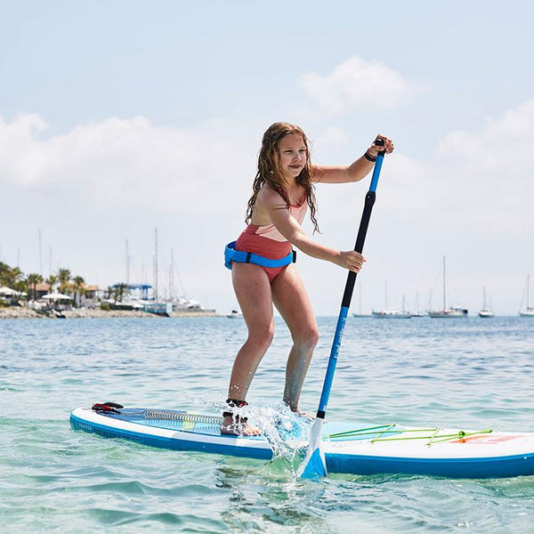 girl paddle boarding using blue Airbelt Personal Flotation Device (PFD)