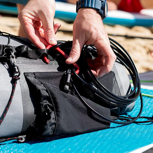 Red Original combination board lock being attached to a deck bag on a sup