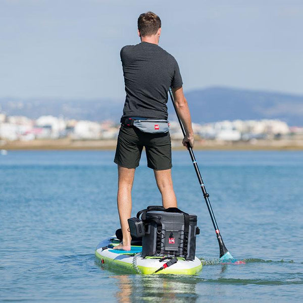 man paddling with the small Red Original cool bag attached to the back of his SUP