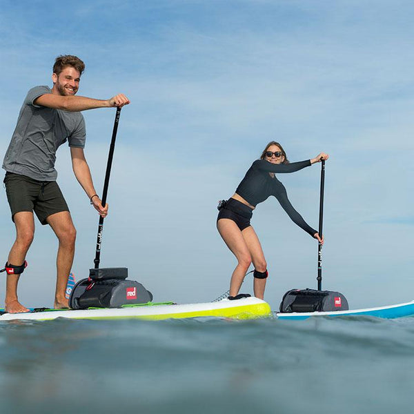 couple paddle boarding with Red Original deck bags on their SUPs