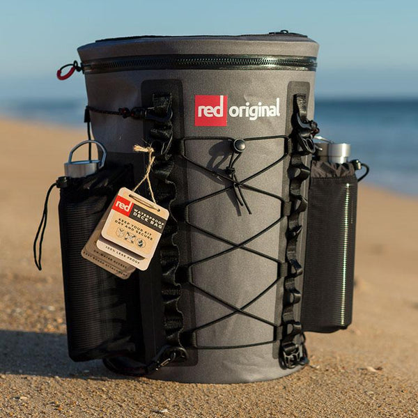 Red Original deck bag on a beach with water bottles in the pockets