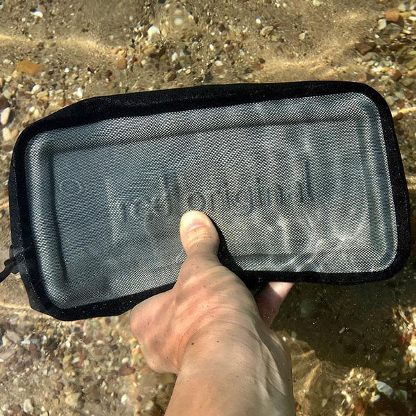 man holding Red Original Waterproof Pouch underwater