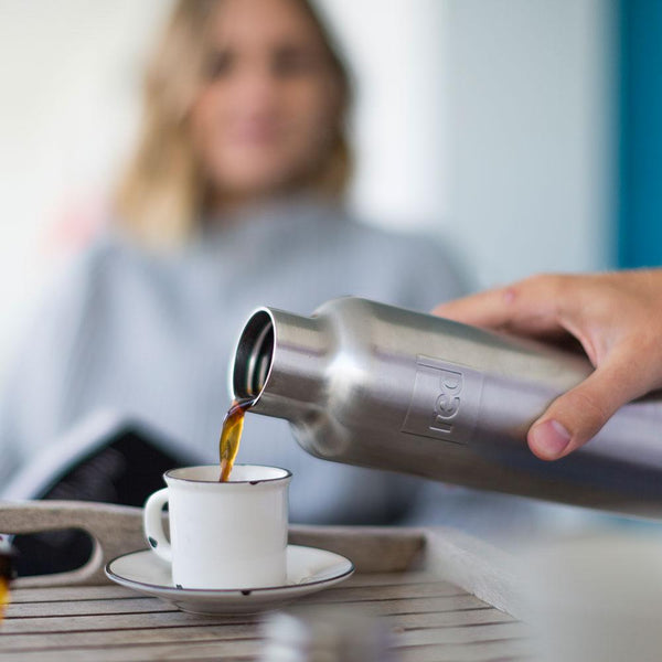 man pouring coffee from a Red Original insulated drinks bottle