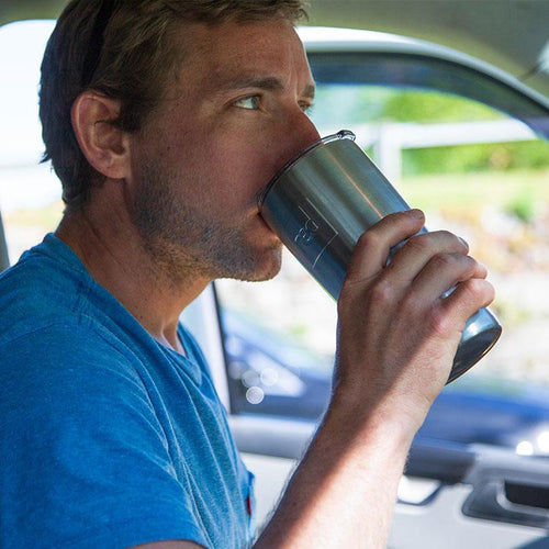 Man Drinking From Travel Cup In A Car