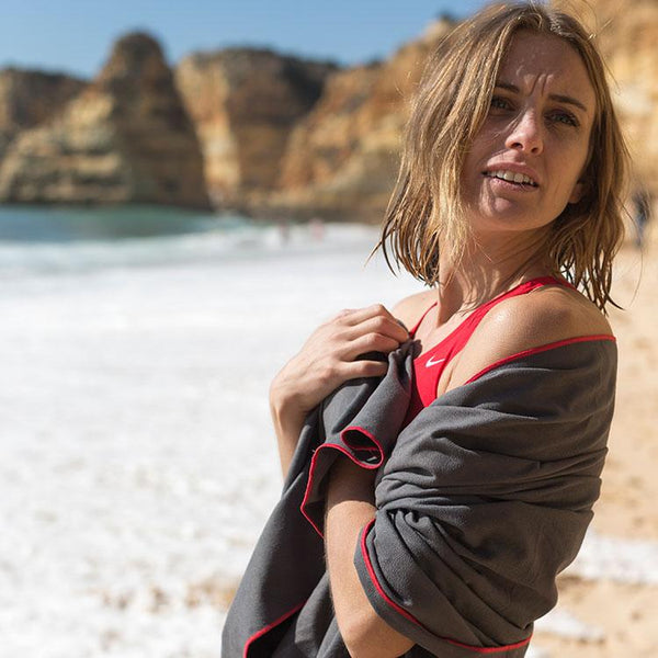 woman drying herself on a beach with Red Original Microfibre Towel