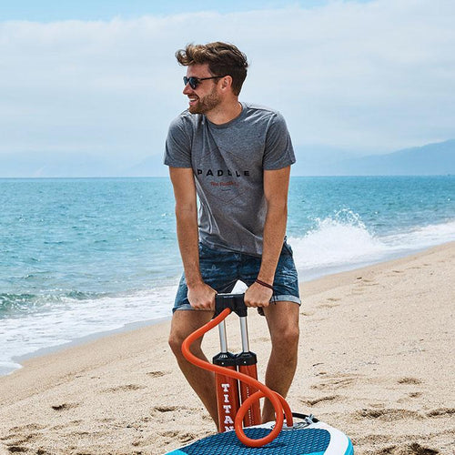 Man pumping up a board wearing a Red Original Paddle On grey t-shirt