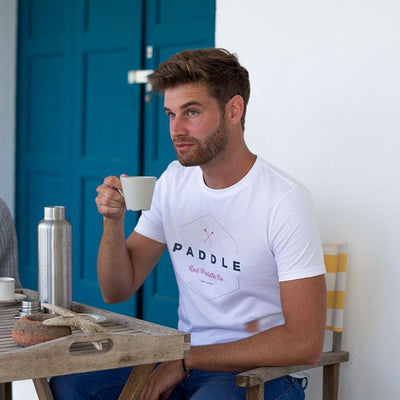 Man drinking coffee wearing the Red Original Paddle On t-shirt in white