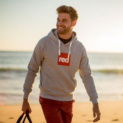 Man on a beach wearing the Red Original Square Logo Hoodie