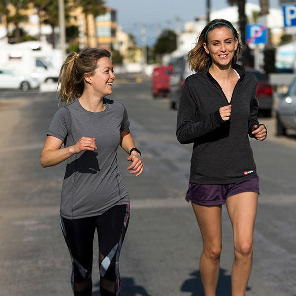 two women running with one wearing the Red Original Women's Performance T Shirt
