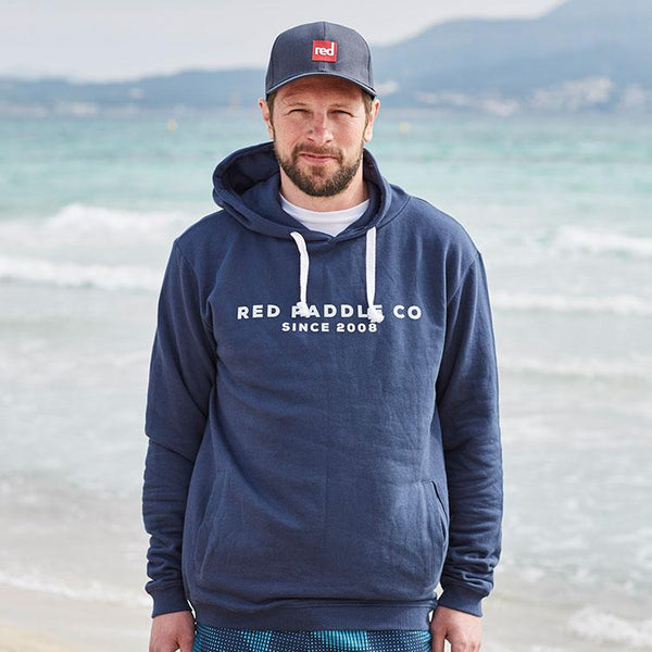 Man on beach wearing Red Paddle Co Since 2008 Unisex Hoodie - Blue