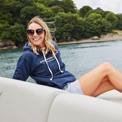 Women sat on boat wearing Red Paddle Co Since 2008 Unisex Hoodie - Blue