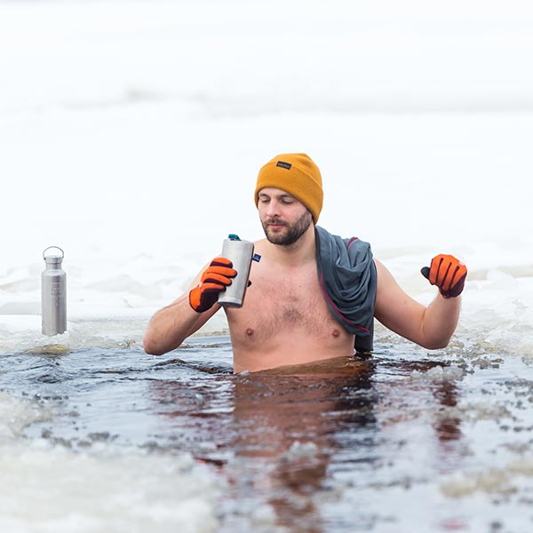 Man wearing orange beanie and drinking from insulated cup in cold water