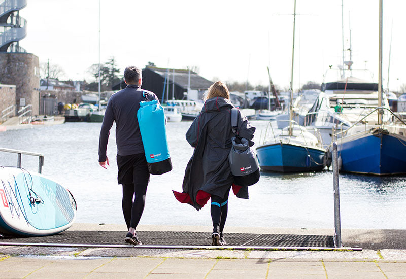 Couple carrying Red Original Roll Top Dry Bags