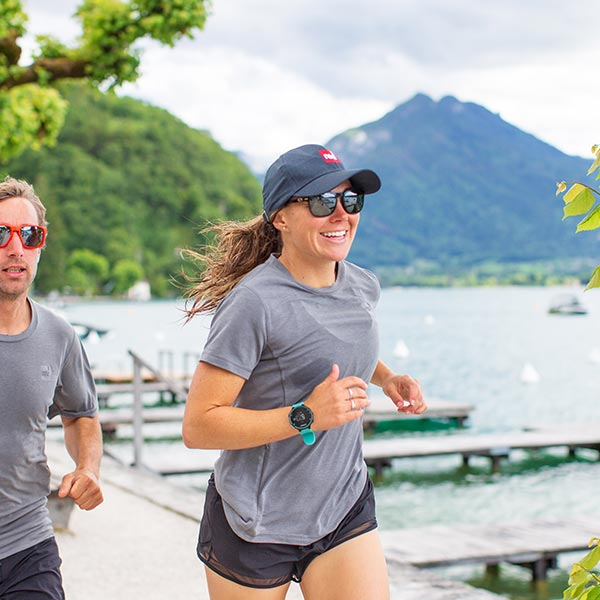 Man and woman wearing Red Original performance t-shirts jogging On a beach