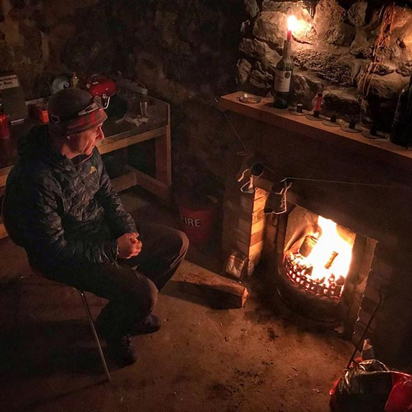 Man Sat Next To a fire in a cottage