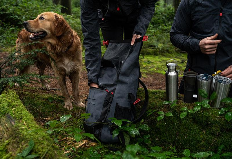 Dog standing next to man and woman rummaging through a bag in the forest