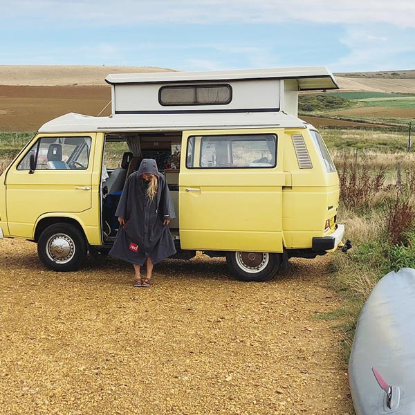 Woman with a campervan wearing a change robe