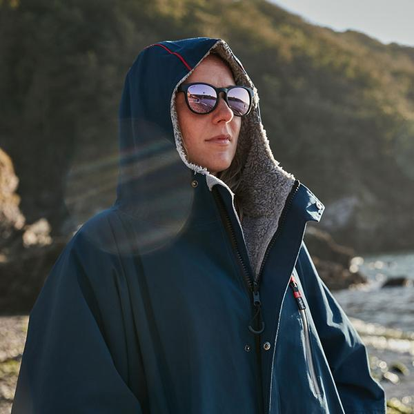 Woman wearing navy long sleeve waterproof changing robe on the beach with the hood up