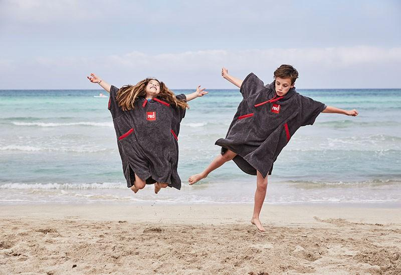 Two kids wearing Kids Poncho towels jumping in the air
