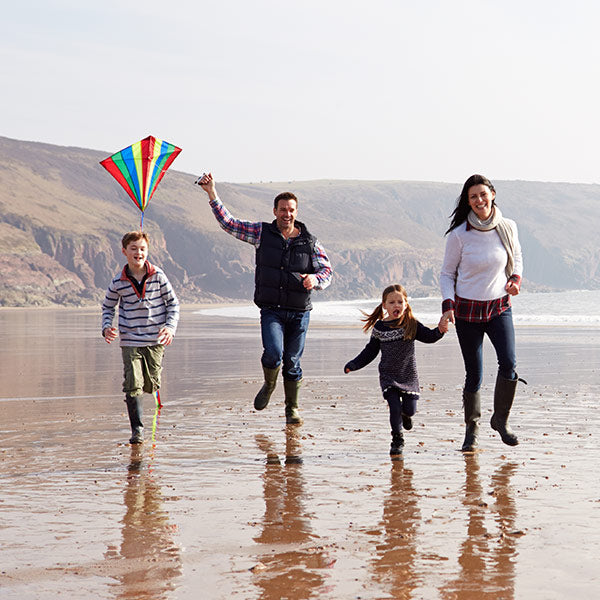 Family on a beach flying a kite