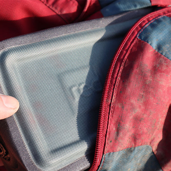 The Red Original Waterproof Pouch being placed into a bag