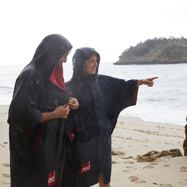 Man and woman on a beach wearing Red Original Pro change Robes with the hoods up