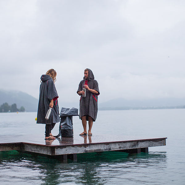 Male and female wearing changing jackets by Lake Annecy