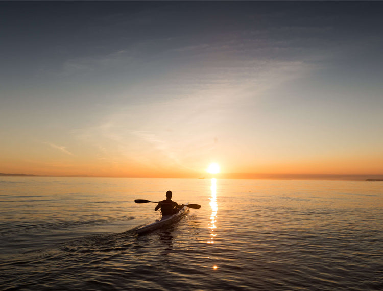 A Man Kayaking Out Into The Sunset