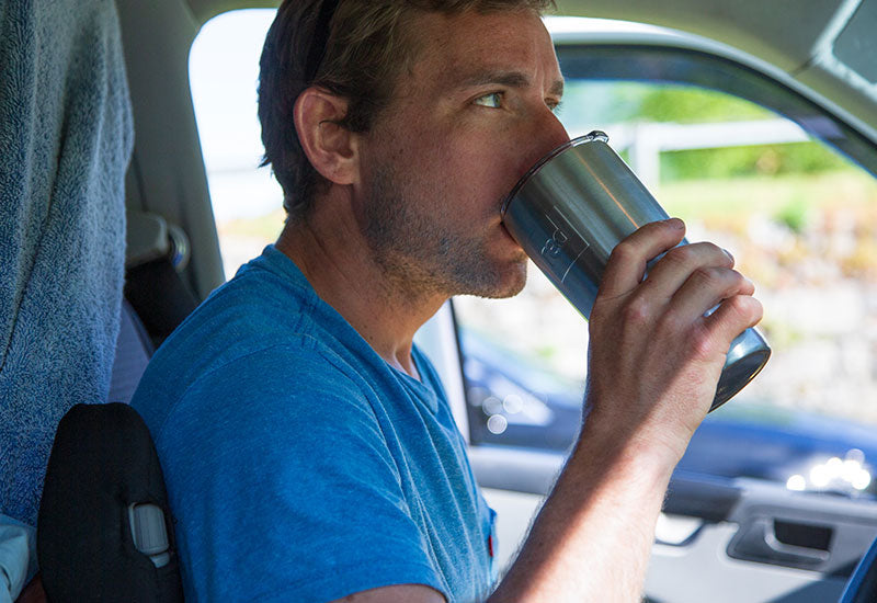 Man Drinking From The Travel Cup In A Car