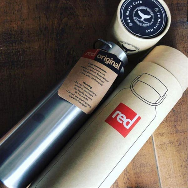 Red Original Insulated Stainless Steel Water Bottle Next To Its Packaging